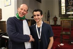 Mr. Price congratulates Julen after he won the school Geography Bee